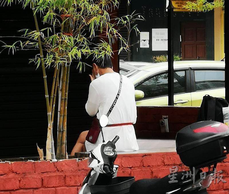 男子坐在店铺的矮墙上,背著马路低头。