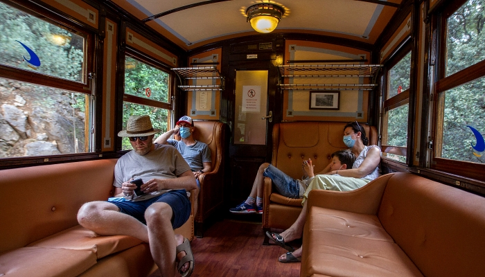Passengers rest aboard the Palma-Soller train in the Spanish Balearic Island of Mallorca. AFP